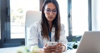 Clinician at a desk on a smart phone