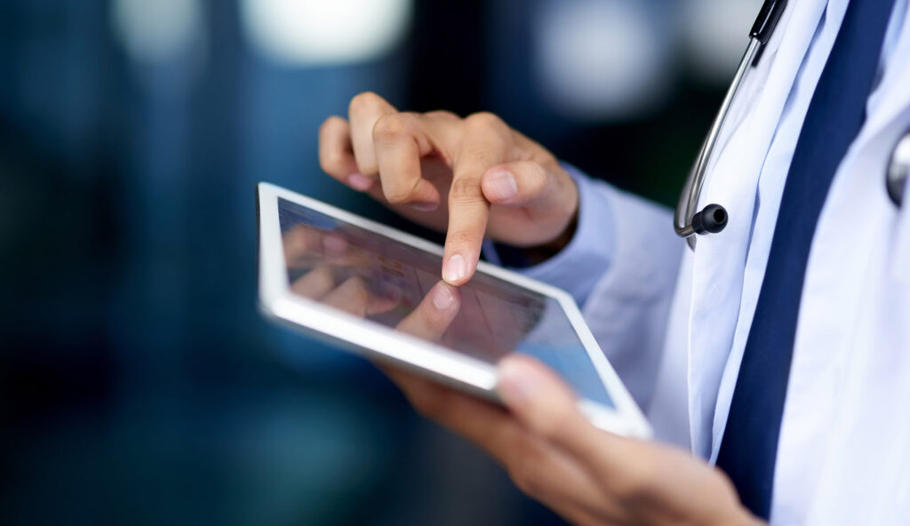 A clinician in a lab coat on a tablet