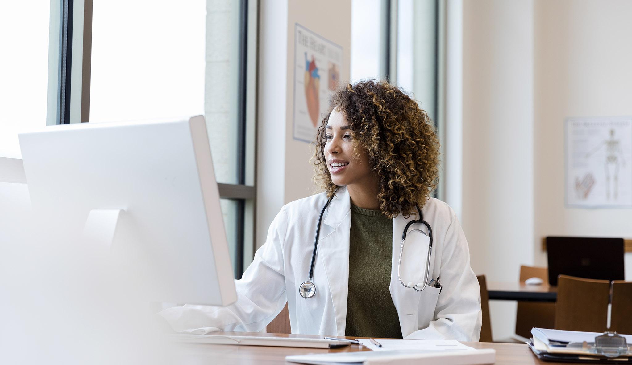 Clinician in a lab coat at a desktop computer
